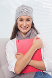 Cheerful brunette with winter hat on holding folder