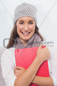 Smiling brunette with winter hat on holding folder