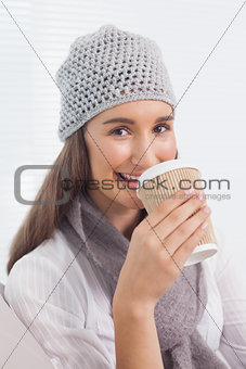 Smiling brunette with winter hat on drinking coffee