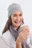 Cheerful brunette with winter hat on holding mug of coffee