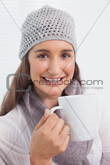 Smiling brunette with winter hat on holding cup of coffee
