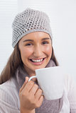 Happy brunette with winter hat on holding cup of coffee