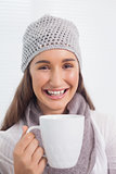 Cheerful pretty brunette with winter hat on holding cup of coffee