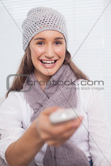 Smiling brunette with winter hat on holding remote