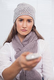 Serious brunette with winter hat on holding remote