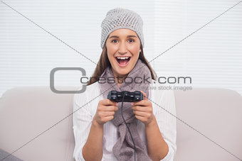 Smiling brunette with winter hat on playing video games