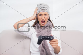 Angry brunette with winter hat on playing video games