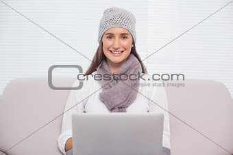 Smiling brunette with winter hat on using her laptop