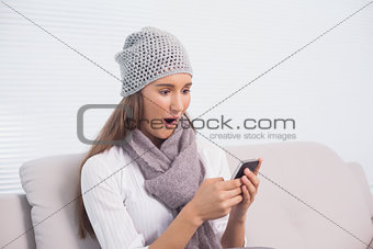Astonished cute brunette with winter hat on using her smartphone
