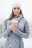 Peaceful pretty brunette with winter clothes on holding coffee
