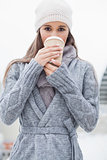 Pretty brunette with winter clothes on drinking coffee