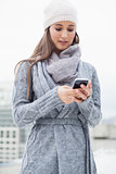 Focused woman with winter clothes on text messaging