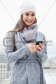 Cheerful woman with winter clothes on text messaging