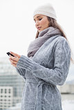 Focused brunette with winter clothes on text messaging