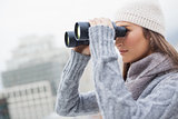 Gorgeous woman with winter clothes on using binoculars