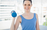 Smiling sporty woman exercising with dumbbell