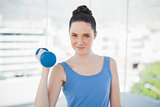 Cheerful sporty woman exercising with dumbbell