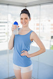 Cheerful slender woman holding plastic flask