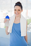 Cheerful slender woman holding plastic flask and sport towel