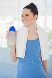 Smiling slender woman holding plastic flask and sport towel