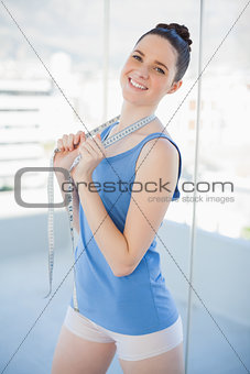 Cheerful gorgeous woman in sportswear holding measuring tape