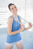 Cheerful slender woman in sportswear holding measuring tape