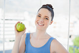 Cheerful slender woman in sportswear holding green apple