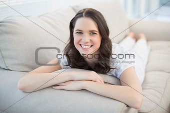 Cheerful pretty woman lying on a cosy couch