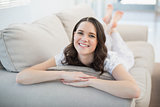 Smiling pretty woman lying on a cosy couch