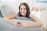 Cheerful pretty woman lying on a cosy couch sending text message