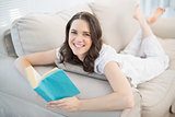 Cheerful pretty woman lying on a cosy couch reading book
