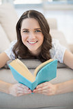 Smiling pretty woman lying on a cosy couch reading book