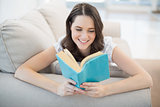Peaceful pretty woman lying on a cosy couch reading book