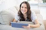 Cheerful woman lying on a cosy couch holding tablet pc