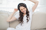 Cheerful young woman dancing while listening to music
