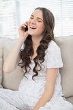 Young woman in pyjamas laughing on the phone