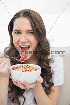 Cute young  woman in pyjamas eating fruity cereal