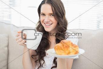 Cute young woman in pyjamas having breakfast
