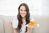 Smiling young woman in pyjamas having breakfast