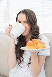 Cheerful young woman in pyjamas having breakfast