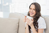 Cheerful young woman in pyjamas having coffee
