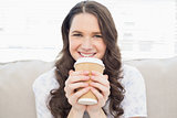 Smiling pretty woman in pyjamas having coffee