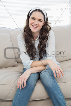 Casual young woman sitting on a cosy couch