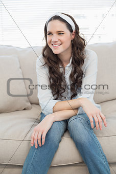 Casual pretty woman sitting on a cosy couch
