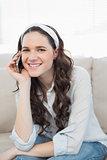 Smiling casual woman sitting on a cosy couch having a phone call
