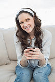 Pretty casual woman text messaging on her smartphone