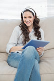 Cheerful casual woman on cosy couch using tablet pc