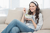 Pretty casual woman on cosy couch eating salad