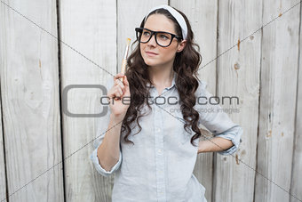 Artistic trendy woman with stylish glasses posing holding paintbrush