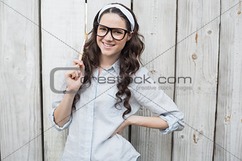 Artistic woman with stylish glasses posing holding paintbrush